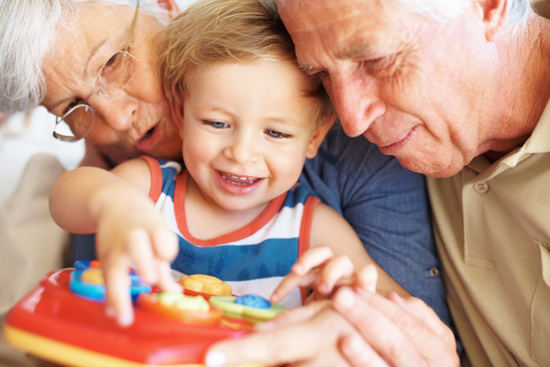 Closeup of boy playing a toy with his grandparents